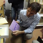 Dr Amir Brito Cadôr (EBA/UFMG), showing books from the special collections archive at UFMG.